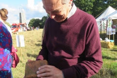 Ian Symes, Parish Council Vice Chairman, examining a brick made on the Common